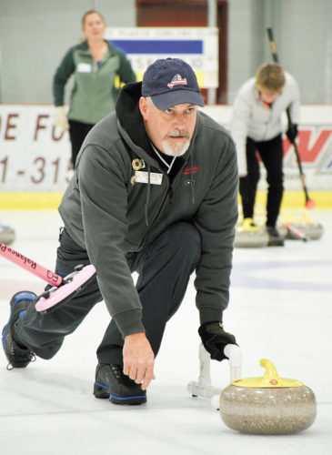 Darren Dalton, president of the Lake Placid Curling Club, releases a stone during a curling match at the Saranac Lake Civic Center. (Enterprise photo — Justin A. Levine)