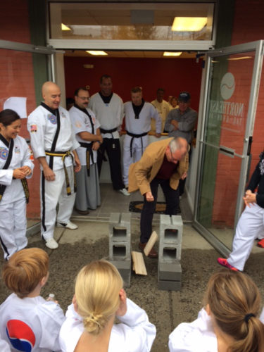 Saranac Lake Mayor Clyde Rabideau breaks a board at the Nov. 5 grand opening of Northeast Taekwondo at 62 Main St. in Saranac Lake. (Photo provided)