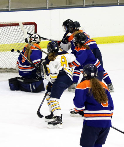 Lake Placid eighth-grader Lydia Bullock charges to the net for her first varsity goal during Tuesday's game at the 1932 Rink against Potsdam. Tess Stanton (8) assisted on the play. Potsdam won the game 11-2. It was the season-opener for the Blue Bombers. (Photo — Alicia Brandes)