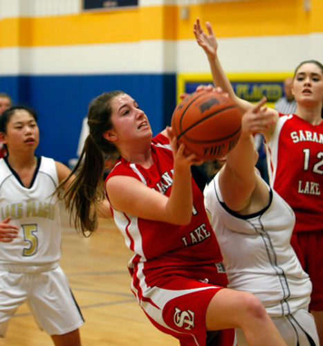 Saranac Lake senior Andrea Boon drives to the basket while Lake Placid's Frankie Hathaway attempts to block her shot during Wednesday's game in Lake Placid.  (Photo — Roy Bombard)