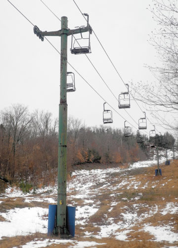 Vacant chairs dangle over the disappearing snow Wednesday on the slopes of the Big Tupper Ski Area in Tupper Lake. (Enterprise photo — Kelly Carroll)