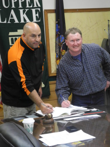 "Trustees David ""Haji"" Maroun and Clint Hollingsworth sign the oath of office for the village of Tupper Lake Board of Trustees  Thursday at the village office.  (Enterprise photo — Kelly Carroll)"