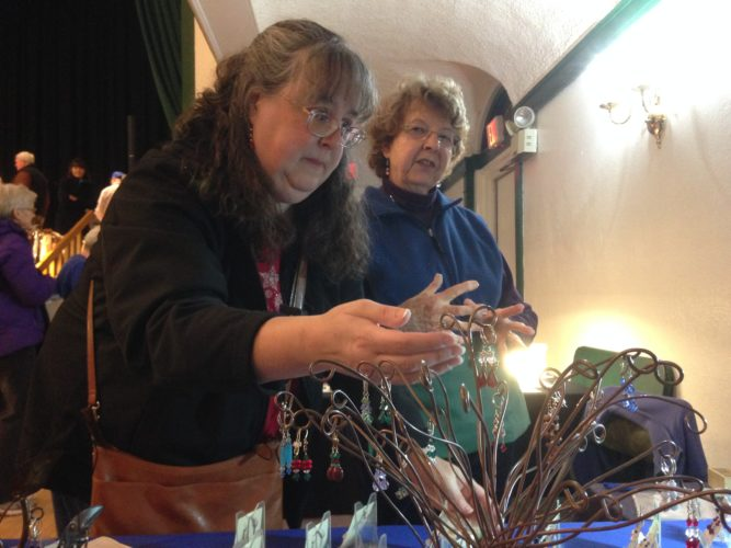 Sandy Fobare of Saranac Lake, left, looks at earrings made by Charlotte Lichtenberg of Keene Valley at the Sparkle Village craft show Friday at the Harrietstown Town Hall in Saranac Lake. The fair continues today from 10 a.m. to 4 p.m.  (Enterprise photo — Peter Crowley)