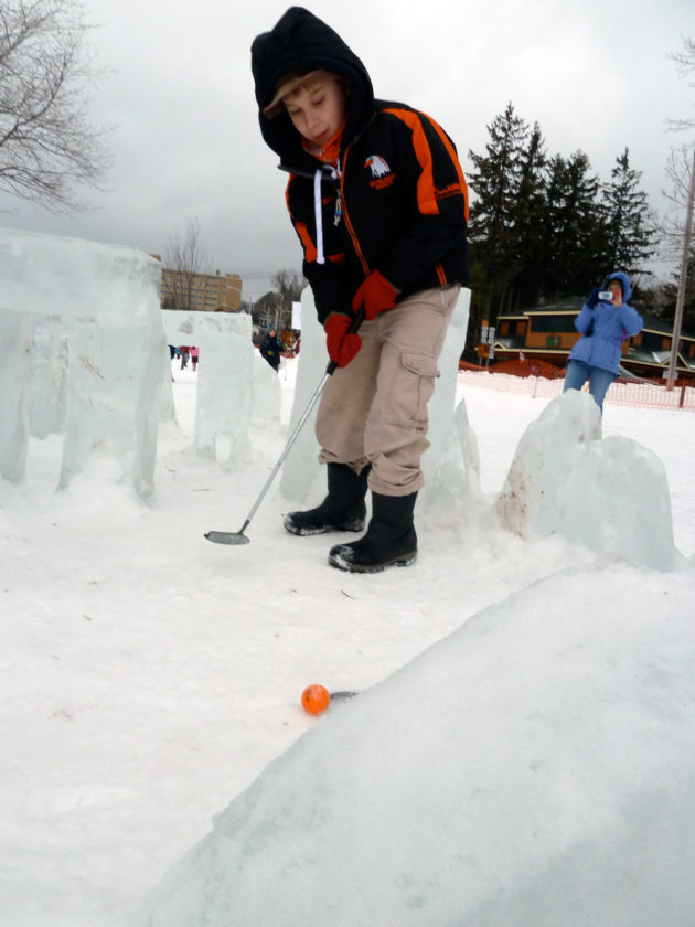 "A boy putts an Arctic Golf ball amid an ice-block Stonehenge, consistent with the ""Celtic Carnival"" theme of the 2014 Saranac Lake Winter Carnival. (Enterprise photo — Peter Crowley)"