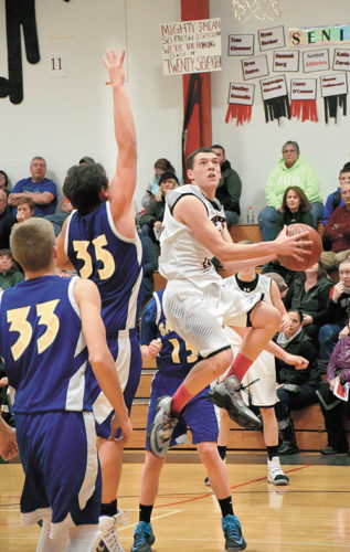 Tupper Lake junior Kameron Sarvis drives to the hoop past St. Regis Falls' Danny Lucey during Monday night's game in Tupper Lake. Sarvis had a team-high 14 points in the game. (Enterprise photo — Justin A. Levine)