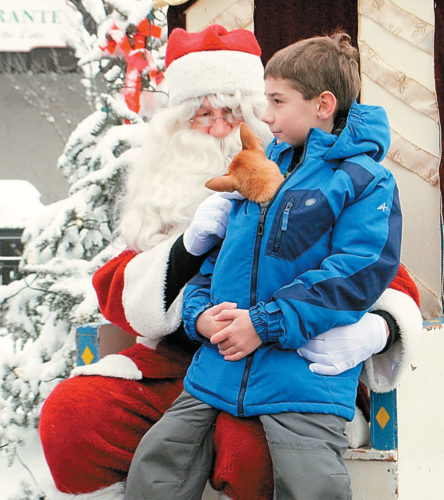 Santa Claus meets with a boy and his dog at Lake Placid's 2014 Holiday Village Stroll. (Enterprise photo — Matthew Turner)