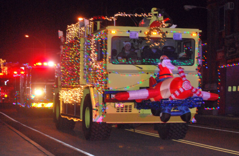 An inflatable Santa Claus in an airplane adorns the front of a brightly lit fire truck from the Adirondack Regional Airport in last year's parade in Saranac Lake. (Enterprise photo — Chris Knight)