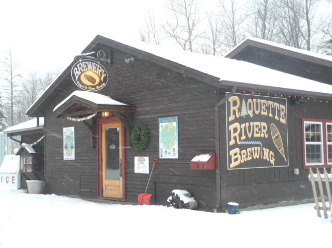 Raquette River Brewing on Balsam Street, covered in snow Monday, will raise funds for the Flanders Performance Park bandshell by hosting eight hours of live music Saturday. (Enterprise photo — Kelly Carroll)