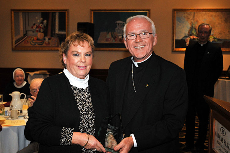 Linda Young, left, of St. Agnes Parish is recognized by Catholic Charities of the Diocese of Ogdensburg at the Oct. 19 Caritas Dinner at the Crowne Plaza in Lake Placid. She was presented with the Catholic Charities Presidential Award for her outstanding works of mercy. Bishop Terry LaValley, right, noted that Young spearheaded the opening of the Ecumenical Food Pantry located at St. Agnes Church in Lake Placid in 1985 and five years latter opened the thrift store at the marina. (Photo provided)