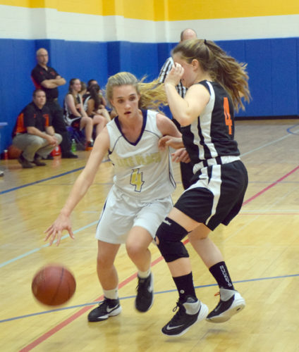 Lake Placid junior Camille Craig drives past Keene's Emily Whitney during Tuesday night's game in Lake Placid. (Enterprise photo — Justin A. Levine)