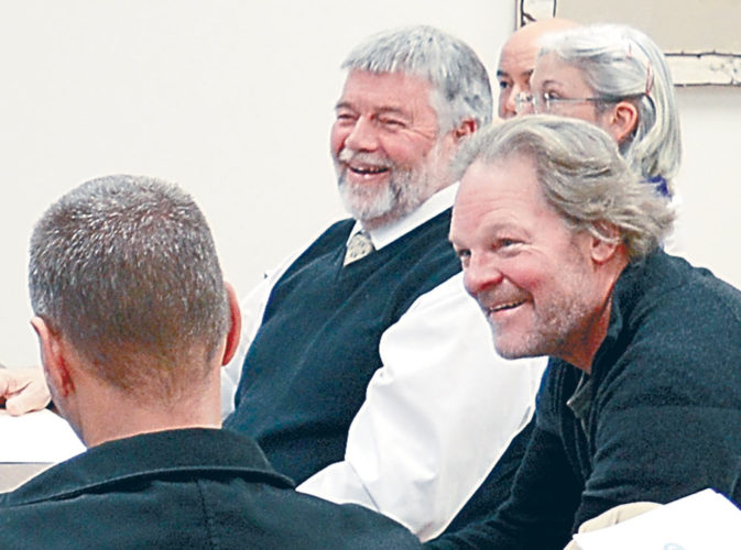 Retired North Elba-Lake Placid Code Enforcement Officer James Morganson, center right, laughs beside village trustees Peter Holderied, right, and Scott Monroe, center, at a joint village and town board meeting Tuesday.  (Enterprise photo — Antonio Olivero)