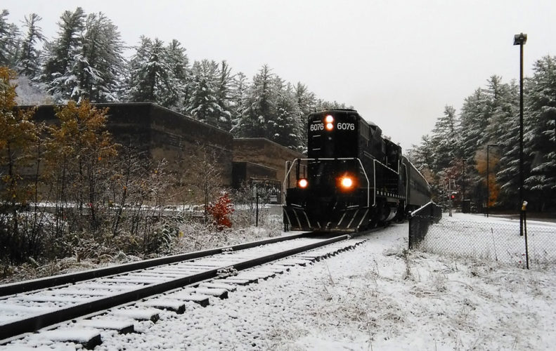 An Adirondack Scenic Railroad train makes one of its last runs of the year — and possibly ever — through North Country Community College's Saranac Lake campus en route to Lake Placid Oct. 22. The state is working on securing legal use or ownership of railroad corridor land parcels at NCCC. (Enterprise photo — Morgan Ryan)