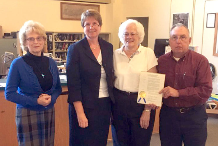 Saranac Lake Central School District Superintendent Diane Fox, second from left, presents members of the Saranac Lake High School Class of 1960 — Barbara Buckley, left, and Mary Lou and Thomas Cassavaugh — with a Commendation of Appreciation for a nearly $6,000 donation to the district's BackPack Program. (Photo provided)