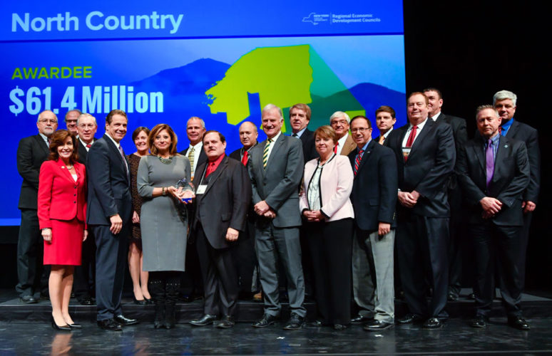A contingent from the North Country accepts a $61.4 million package of Regional Economic Development Council grants from state officials including Gov. Andrew Cuomo and Lt. Gov. Kathy Hochul today at the Egg in Albany. At left center, North Country REDC co-Chairman Garry Douglas accepts a trophy from broadcast journalist Maria Bartiromo, who announced each of the award winners. (Photo provided by the governor's office)