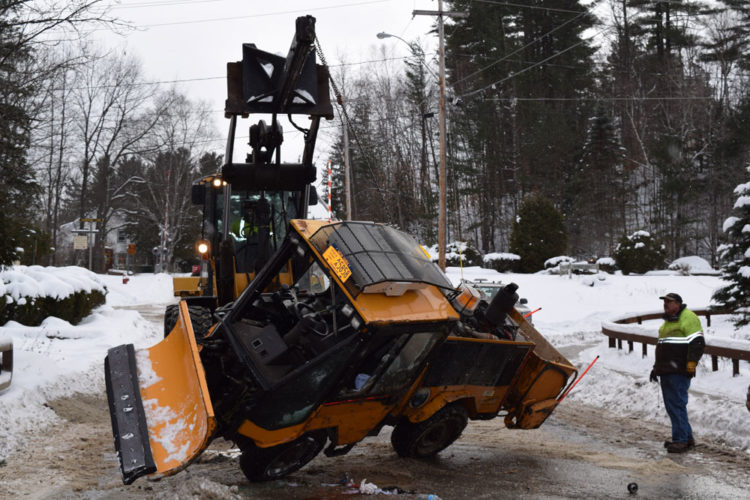 Village of Saranac Lake employees work to get the village sidewalk plow upright after it crashed Friday morning on Pine Street. (Enterprise photo — Chris Knight)