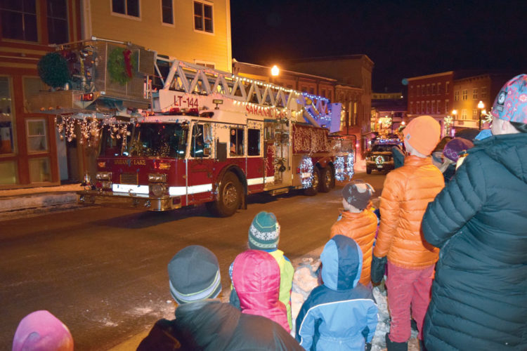 A crowd of people next to the Berkeley Green Friday night watches the Saranac Lake Volunteer Fire Department's snorkel truck, which featured lights synchronized to Christmas music and was judged the best decorated vehicle in the department's third annual Lighted Fire Truck Parade. The parade, sponsored by HomEnergy Services, included a dozen trucks decorated for the holidays from local fire departments and as far away as Peru, New York. (Enterprise photo — Chris Knight)