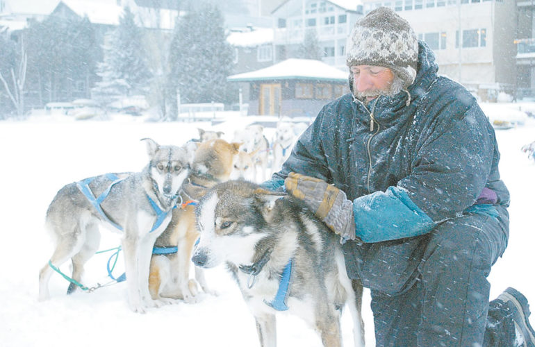 John Houghton, the owner of Thunder Mountain Dog Sled Tours, poses with his dogs on Mirror Lake in 2015.  (Enterprise photo —Matthew Turner)