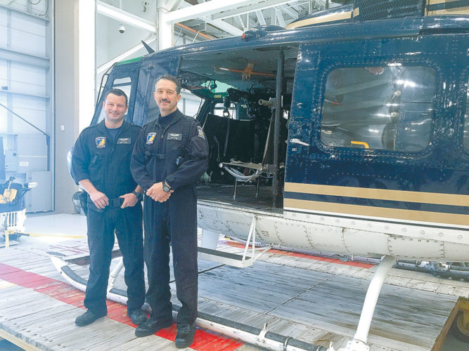 New York State Police Tech. Lt. Peter Mclain, right, and Tech. Sgt. Brian Rumrill stand next to the Huey helicopter they used to rescue a pair of missing hikers from Algonquin Peak Tuesday. (Photo courtesy of the New York State Police)