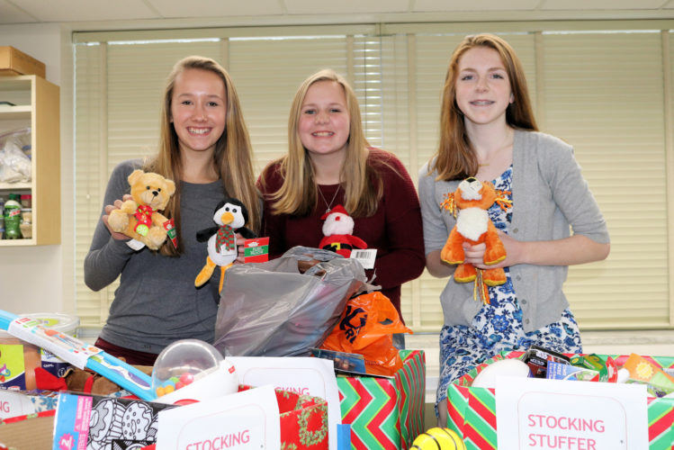 Saranac Lake High School freshmen class officers display some of the items they collected in their Stocking Stuffer Drive. The class of 2020 sponsored a competition among the school's homerooms to see which one could collect the most items to benefit Toys for Tots. The top three homerooms were awarded with platters of holiday cookies. Pictured are class officers Sylvie Linck, Emily Muncil and Emma Peer. (Photo provided)