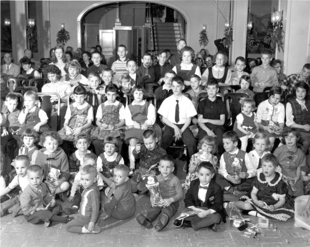"This picture was taken at the Ray Brook State Hospital's annual Christmas party around 1966. The photo was given to me by Jerry Cavallo some time ago and he has been very ""aggressive"" in his urging me to publish it because his pal and our son, Keegan John Riley is seated in the front row in the bow tie. Looking at the photo, to the left of Keegan, skipping one kid, are our twin sons, Kean Matthew and Kasey Mark. Their grandmother was Annabelle Gauthier who worked at the hospital. She was married to a twin named Clifford Gauthier, his brother was named Clifton ... so the twins' grandfather was a twin. When I was a kid and we lived at the Oseetah Dairy Farm in Ray Brook, there were weekly movies at the hospital every week that the locals were invited to attend. There are about 50 local kids in this picture, many who probably still live in Saranac Lake.                                          (Photo provided)"