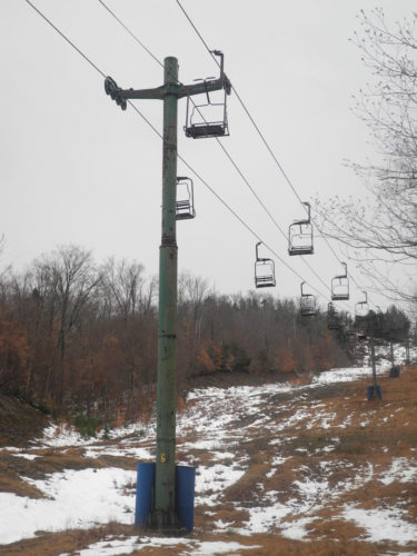 Vacant chairs dangle over the disappearing snow in December on the slopes of the Big Tupper Ski Area in Tupper Lake.  (Enterprise photo — Kelly Carroll)
