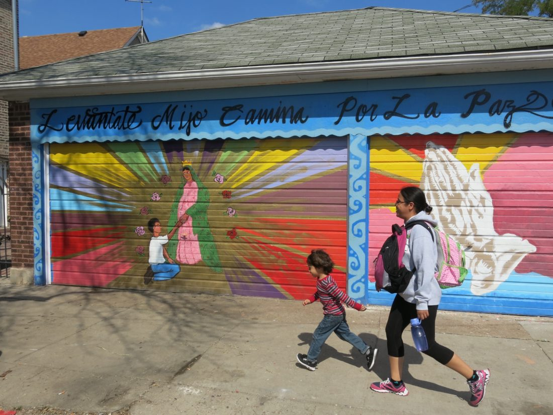 "Family members walk home from school in Chicago's Little Village, where most people live within walking distance of schools. Murals, many with religious themes, have been painted on many buildings in the community. This garage has been inscribed, ""Rise up, my son, and go in peace.""  (Photo copyright by Philip Langdon, used with permission)"