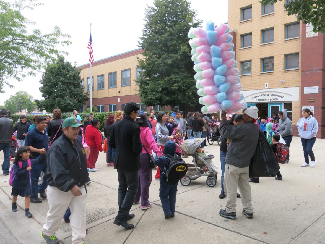 Parents pick up their children at Josefa Ortiz de Dominguez Elementary School as a vendor sells cotton candy in the Little Village, Chicago. Many children walk home with their mother or father.   (Photo copyright by Philip Langdon, used with permission)