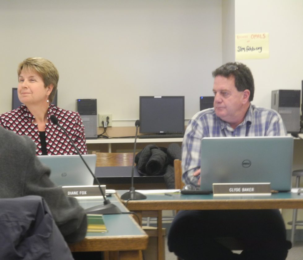 Superintendent Diane Fox and board president Clyde Baker discuss procedures in regard to a donation of baseball uniforms at yesterday's board meeting. (Enterprise Photo — Kelly Carroll)