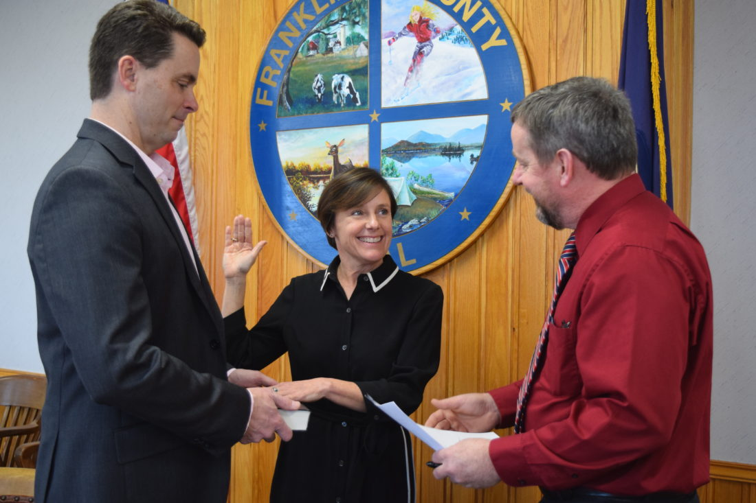 Barbara Rice of Saranac Lake, center, smiles Thursday as she's sworn in as the first chairwoman of the Franklin County Legislature by county Clerk Kip Cassavaw. At left is Chad McCarthy, Rice's husband. (Enterprise photo -- Chris Knight)