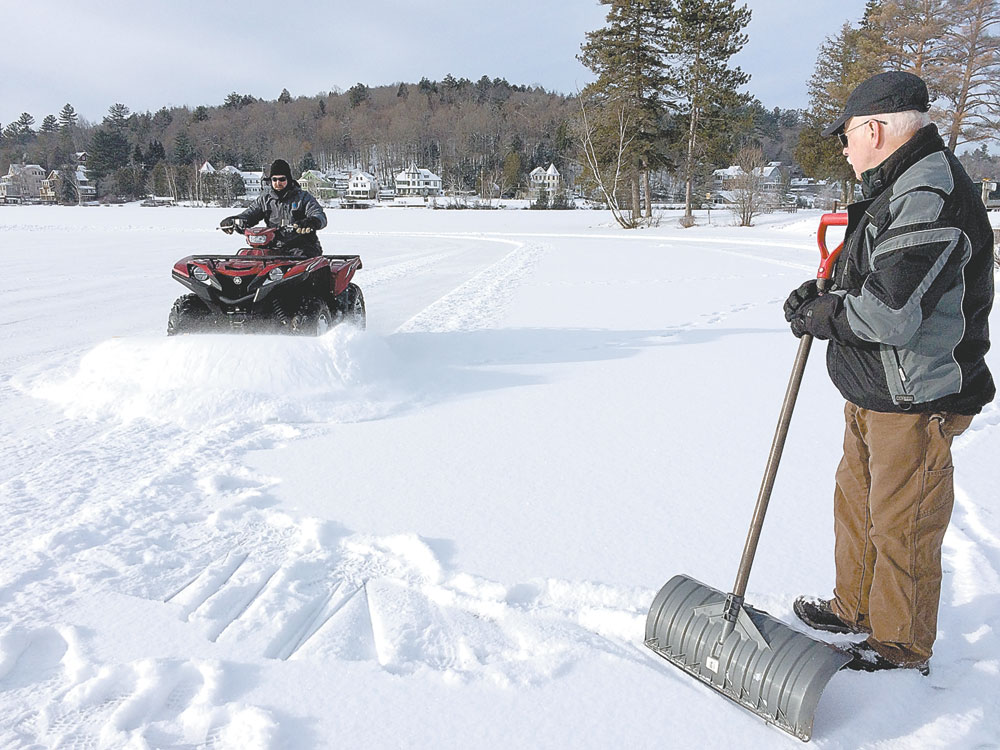 Dean Baker, right, head of the Saranac Lake Winter Carnival Ice Palace building team, watches Saturday as Michael Knapp plows snow off of Pontiac Bay, where ice blocks for the palace are cut each year. The ice was 8 inches thick at the center of the bay, and 8.5 inches thick at the edges, when the picture was taken. Builders typically wait for 12 inches of ice before starting construction of the palace. (Photo provided — Colleen O'Neill)