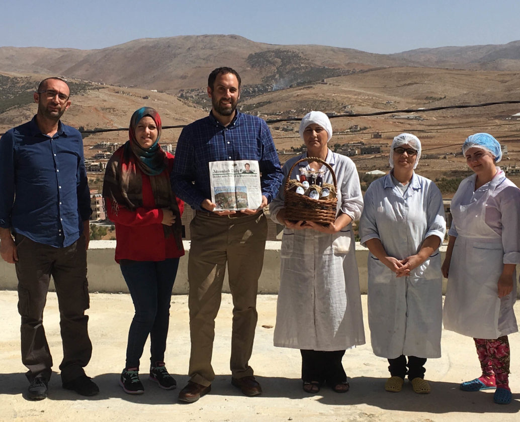 Saranac Lake resident Ezra Schwartzberg, holding a copy of the Enterprise, stands with (right) members of the Morning Star Cooperative in El Maideh, Lebanon, and (left) employees of the Lebanon Reforestation Initiative. The employees presented Schwartzberg with a gift of products produced by the cooperative using herbs and agricultural products grown by local producers or foraged on the village's public lands.(Photo provided)