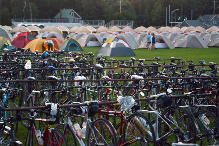 Cycle Adirondacks rider's bikes and tents are lined up neatly in the Petrova School field during their two-night stay in Saranac Lake in August 2016. (Enterprise photo — Lou Reuter)