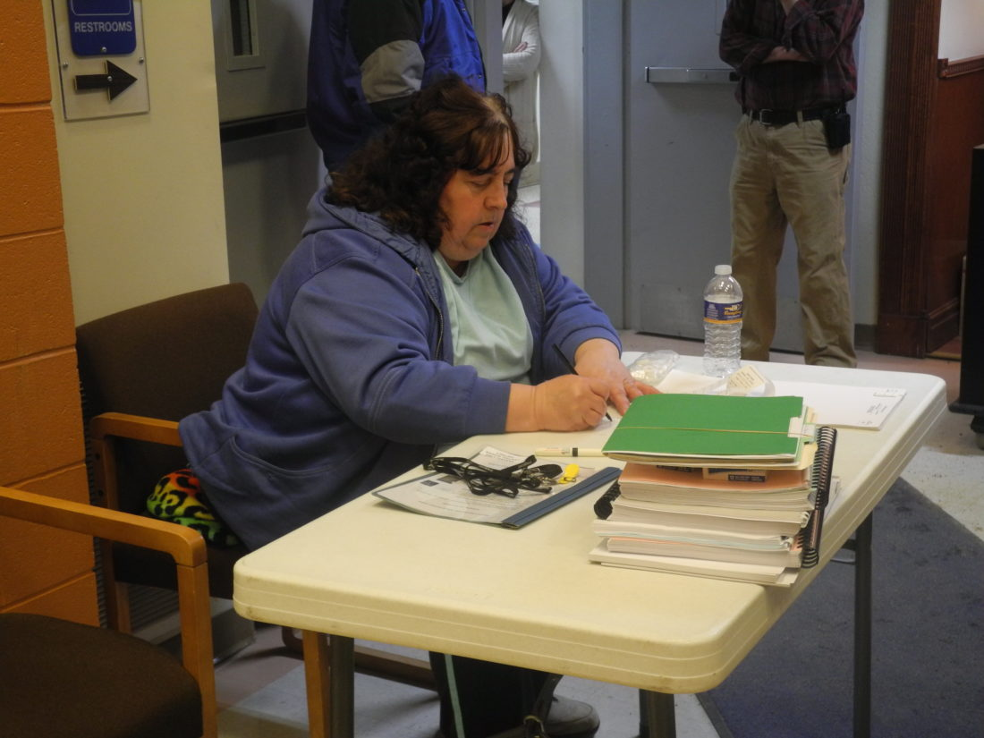 Kim Fitzgerald reads aloud tallies from the capital project vote at Saranac Lake High School Tuesday night. (Enterprise photo — Kelly Carroll)