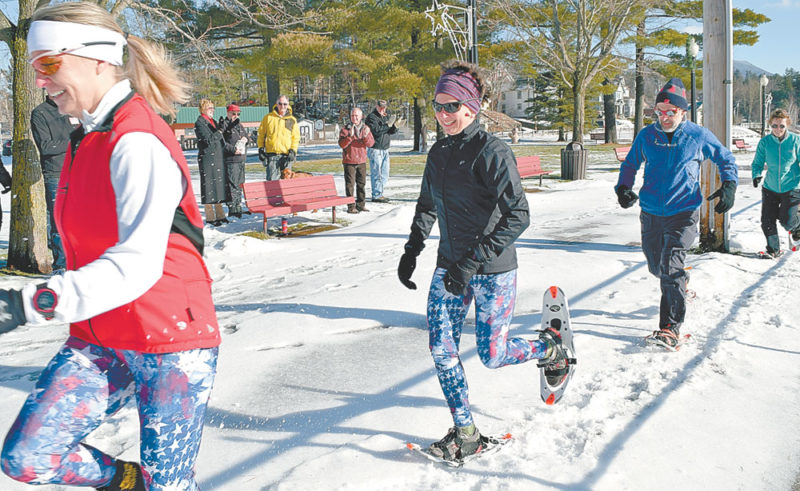From left, Elizabeth Trachte of Lake Placid, Diana  Billingsley of Lake Clear and other snowshoers track through the snow along the edge of Riverside Park in Saranac Lake Wednesday as part of a kick-off for the village's hosting of the Feb. 25 World Snowshoe Championships. The park will be the finish line for both the 10k and 5k races. (Enterprise photo — Chris Knight)