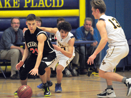 Keene's Azriel Finsterer dribbles the ball while Tony Matos and Stuart Baird close in on defense for Lake Placid during Wednesday's game. (Enterprise photo — Lou Reuter)