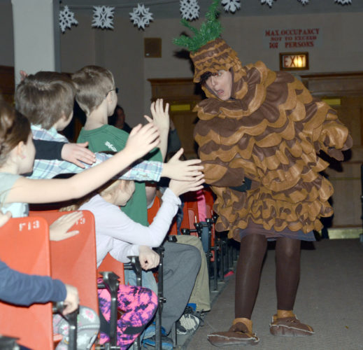 Bruce the Spruce, an evergreen cone who is the mascot for next month's World Snowshoe Championships in Saranac Lake, greets young students while sauntering down the middle aisle of the Petrova Elementary School auditorium during an assembly Friday morning when the mascot was unveiled. Students from Bloomingdale were presented with certificates after they won the contest for naming the mascot. Saranac Lake Middle School art teacher Maria DeAngelo portrayed Bruce. The snowshoe event will be held Feb. 24 and 25. (Enterprise photo — Lou Reuter)