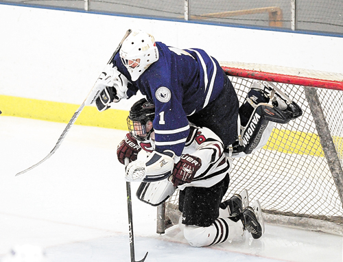 Northwood goalie Mathew Petizian goes airborne into the net after getting taken out by a sliding Michael Shumacher of Shattuck-St. Mary's during the second period of Friday's game. (Enterprise photo — Lou Reuter)