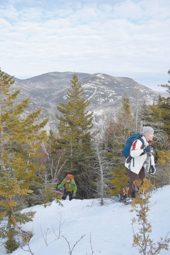 Hollis Tyndall, right, and Mike Primeau emerge from the trees onto the open shoulder of Round Mountain during The Mountaineer's annual Adirondack International Mountaineering Festival in Keene Valley. (Enterprise photo — Justin A. Levine)