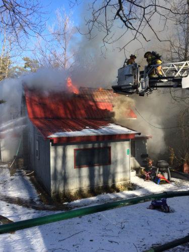 Saranac Lake firefighters battle a blaze at 52 Lake St. this morning. (Enterprise photo — Chris Knight)