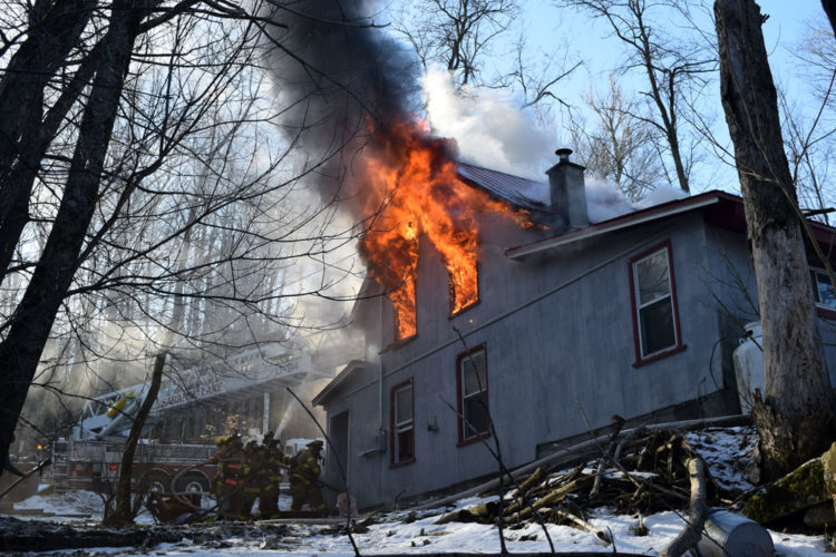 Fire and smoke climb into the sky from the second-story windows and attic of a house at 52 Lake St. in Saranac Lake Monday morning. (Enterprise photo — Chris Knight)