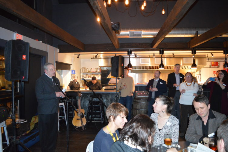 Jim McKenna, the CEO of the Lake Placid-based Regional Office of Sustainable Tourism, speaks in front of a packed room at Big Slide Brewery & Public House during Monday night's annual ROOST Winter Social. (Enterprise photo — Antonio Olivero)