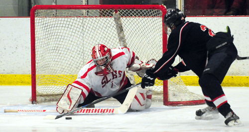 Red Storm sophomore goalie Jaden Gladd pokes the puck away from Larries forward Peyton Felix during the third period of Monday's game. (Enterprise photo — Lou Reuter)