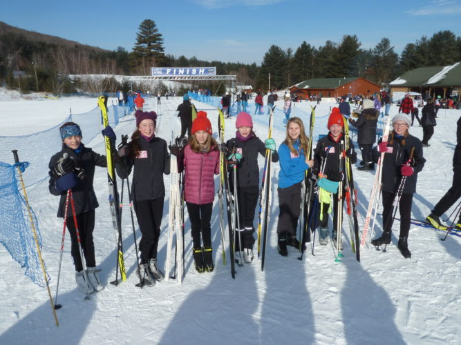Members of the modified nordic ski team from Saranac Lake Middle School pose in front of the finish line of the Queensbury Invitational race Saturday, Jan. 7 at the North Creek Ski Bowl — in which the Saranac Lake boys and girls modified teams placed first in a highly competitive field. From left are Evelyn Eller, Eleanor Crowley, Ruby Smith, Katie Samperi, Bethany Clark, Dellice Chase and Dayna Bearce. Not pictured are teammates Helena Dramm, Leena Keel, Lydia Wamsganz and Emma Wood. (Enterprise photo — Peter Crowley)