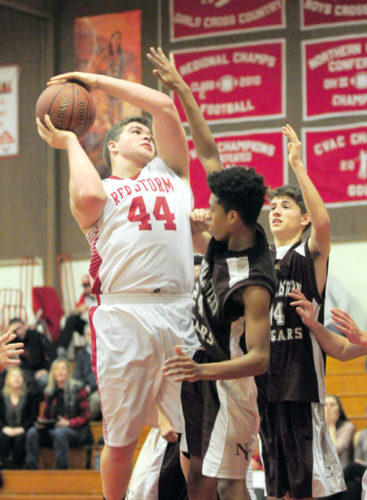 Saranac Lake junior Sean Lincoln goes up for a second-half shot against Northeastern Clinton defender Zavion Beasley (24) while Jacob Mossey of NCCS follows the play in the background Thursday night at Saranac Lake High School. (Enterprise photo — Lou Reuter)