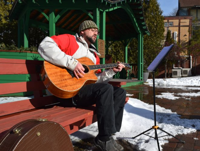 Josh Clement sings and plays guitar in Saranac Lake's Berkeley Green around noon Friday during the inauguration of President Donald Trump. (Enterprise photo — Chris Knight)