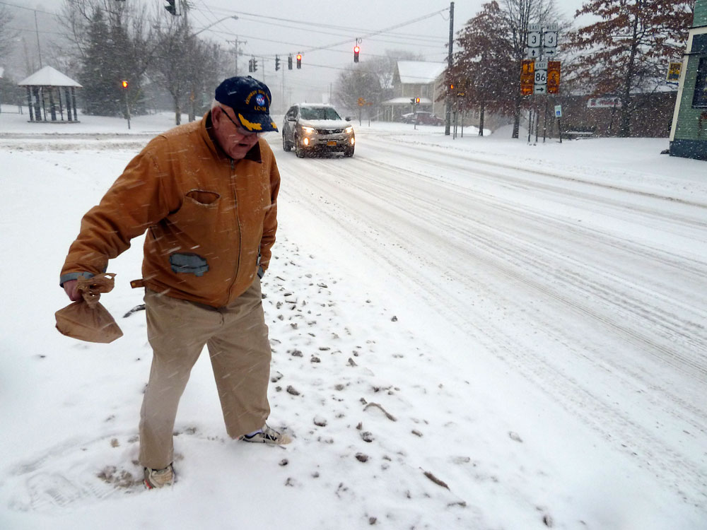 "Jerome ""Champ"" Branch steps carefully this morning as he crosses Bloomingdale Avenue in front of Stewart's Shop in Saranac Lake. Freezing rain earlier in the morning changed to snow in some parts of the Adirondacks. (Enterprise photo — Peter Crowley)"