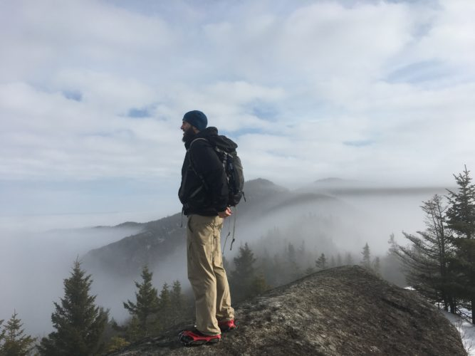 Logan Reidsma of Syracuse looks out at the clouds beneath while hiking the ridge across Jay Mountain Sunday. (Enterprise photo — Antonio Olivero)