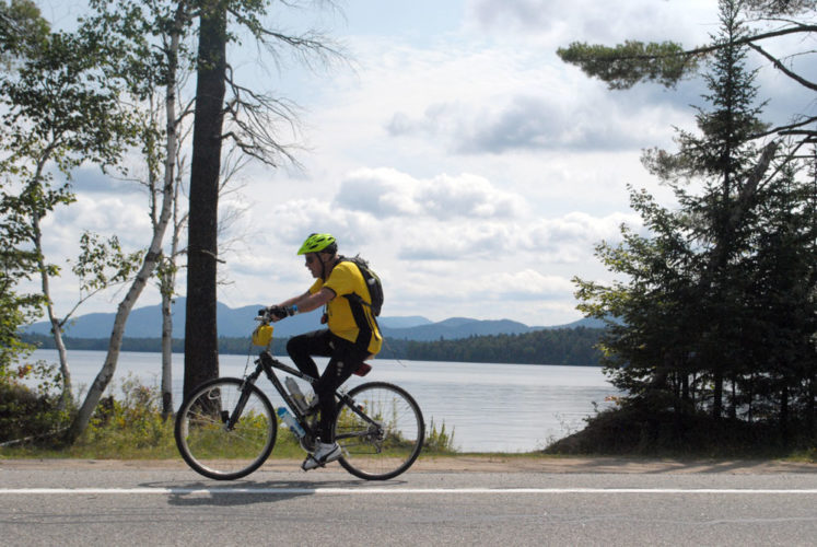 A bike rider approaches Saranac Lake during Cycle Adirondacks in August 2015, the event's first year. (Enterprise photo — Matthew Turner)