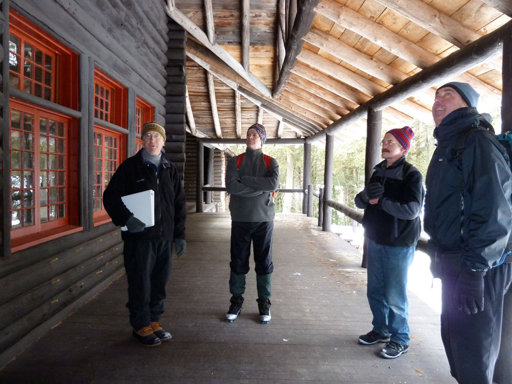 From left, Steven Engelhart, executive director of Adirondack Architectural Heritage, talks about the history of Great Camp Santanoni while standing on its main lodge front porch in February 2012 with Joe Martens, then commissioner of the New York State Department of Environmental Conservation, Schenectady Daily Gazette reporter Stephen Williams and Mike Carr, then executive director of The Nature Conservancy's Adirondack Chapter. (Enterprise photo — Peter Crowley)