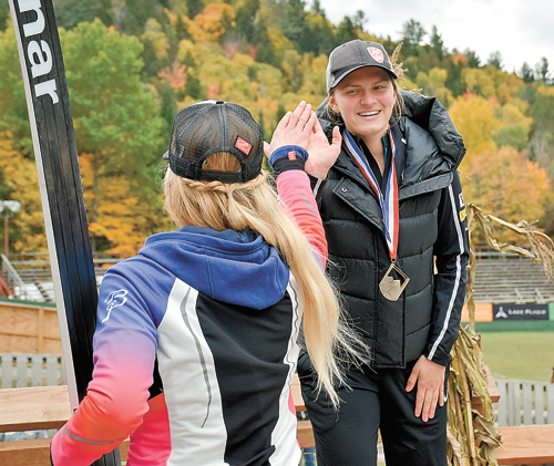 Gabby Armstrong high-fives Tara Geraghty-Moats from the third-place spot on the podium during October's Flaming Leaves Festival. Geraghty-Moats took the gold medal in the competition and Lake Placid native Nina Lussi claimed the silver. (Enterprise photo — Justin A. Levine)